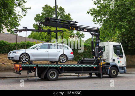 An illegally parked car being hoisted onto a lorry for removal, Hampstead Lane, London, UK - Stock Photo