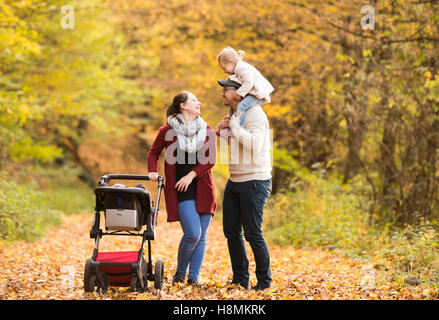 Beautiful young family on a walk in autumn forest. - Stock Photo