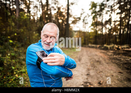 Senior runner in nature with smart phone and earphones. - Stock Photo