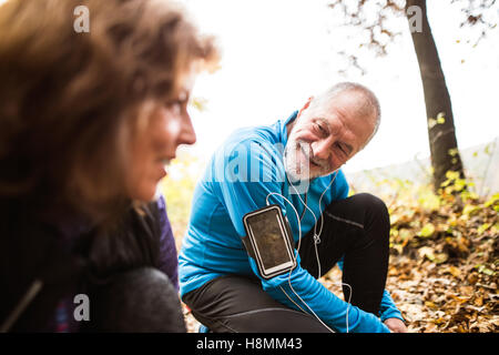 Senior runners in nature, tying shoelaces. Man with smartphone. - Stock Photo