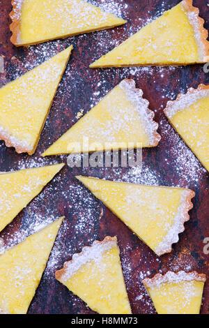 Homemade Lemon Tart slices on slate - Stock Photo