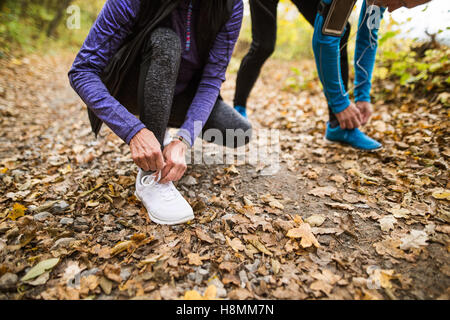 Unrecognizable runners in nature, tying shoelaces. Man with smar - Stock Photo