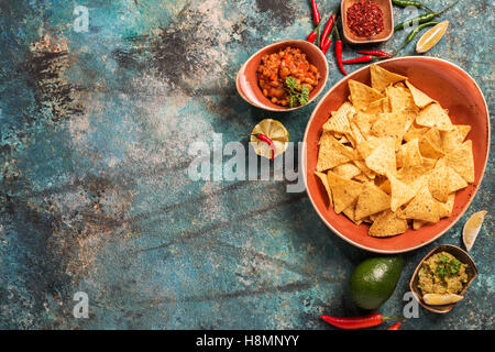 Nachos in plate with guacamole, ground beef and other sauces on blue stone background, top view - Stock Photo