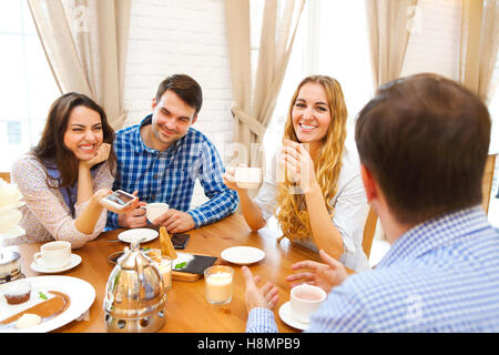 Group of four happy friends meeting and talking and eating desserts on a table at home - Stock Photo