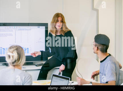 Business woman giving presentation in office - Stock Photo