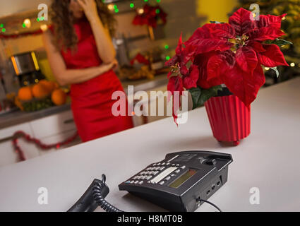 Closeup on phone on kitchen desk and stressed woman in background - Stock Photo
