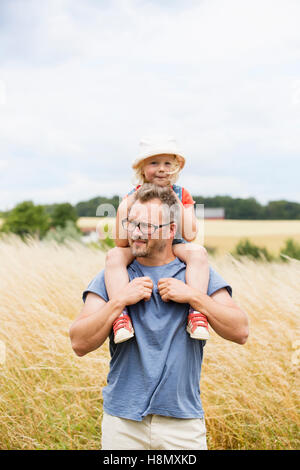 Portrait of father giving daughter (4-5) piggyback ride in field - Stock Photo
