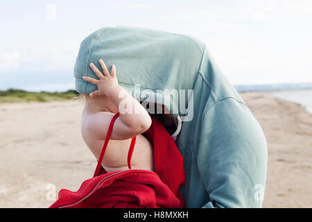 Girl (2-3) hiding in father´s hooded shirt - Stock Photo