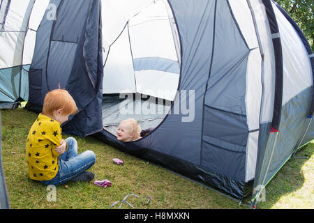 Boy (6-7) playing with sister (2-3) in tent - Stock Photo