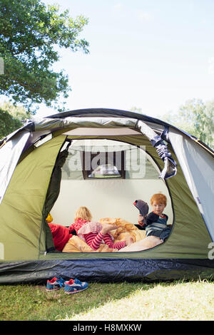 Brother (4-5) and sister (6-7) in tent - Stock Photo