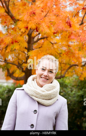 Young woman wearing overcoat against autumn tree - Stock Photo