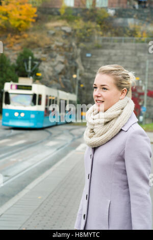 Young woman wearing overcoat with tram in background - Stock Photo