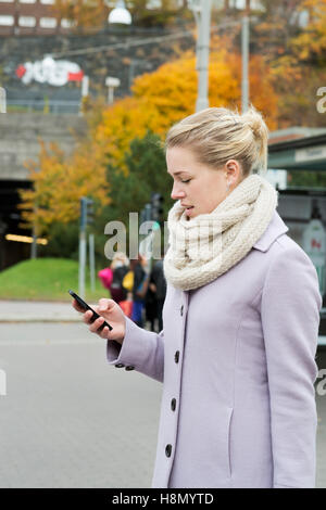 Young woman wearing overcoat using smart phone in street - Stock Photo