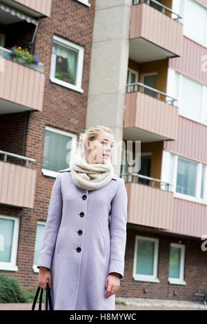 Young woman wearing overcoat standing against buildings - Stock Photo