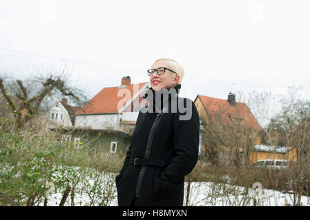 Blonde woman wearing overcoat standing against houses - Stock Photo
