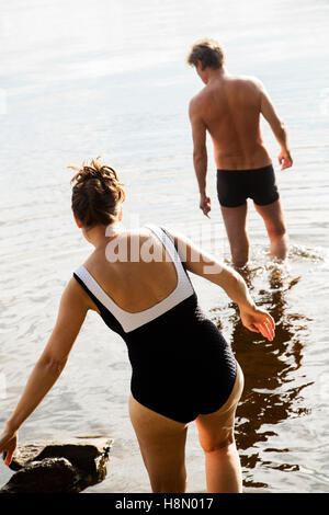 Mature woman and man wading in lake - Stock Photo