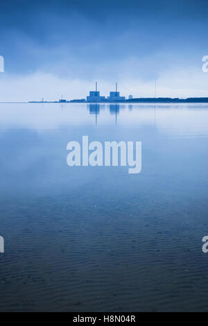 Abandoned nuclear power plant reflected in strait at dawn, Sweden, Skane, Barseback - Stock Photo