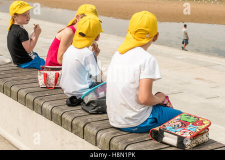 Four young children in yellow hats sitting on a wall on the seafront  in Margate, Kent, eating their packed lunches. - Stock Photo
