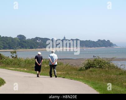 Elderly couple walking along Weston Parade, Weston Shore  Woolston, Southampton, Hampshire UK, with Royal Victoria - Stock Photo