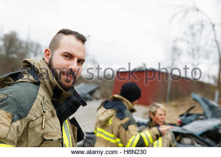 Firefighter looking at camera and others standing beside car - Stock Photo