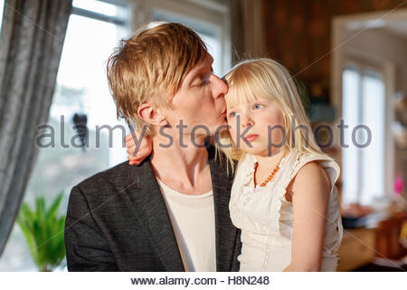 Portrait of man kissing daughter (4-5) - Stock Photo