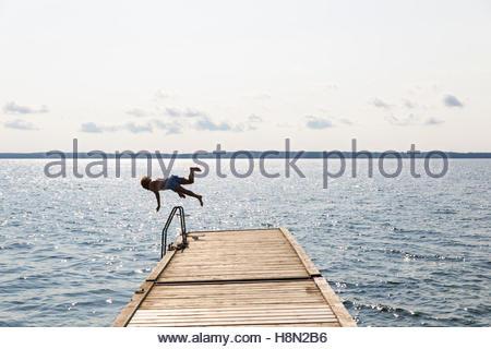Man jumping off jetty into lake - Stock Photo