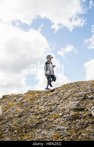 Boy (6-7) walking on top of cliff - Stock Photo