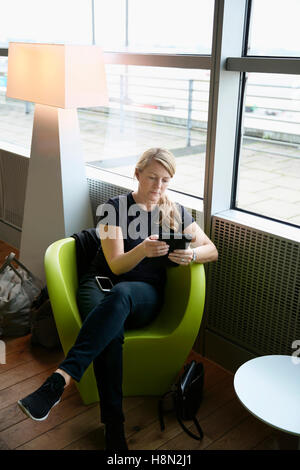 Mature woman sitting at airport hall and using tablet - Stock Photo