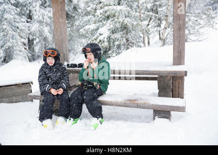 Boys (6-7, 8-9) wearing helmets and goggles sitting on bench surrounded by winter landscape - Stock Photo