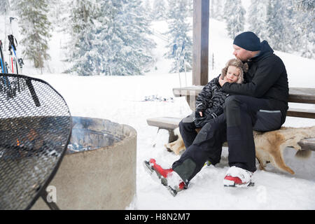Mature man hugging boy (6-7) sitting on bench by bonfire surrounded by winter landscape - Stock Photo
