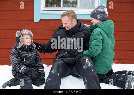 Mature man and boys (6-7, )(8-9) sitting on snow next to wooden cottage wall - Stock Photo