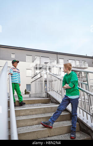 Boys (8-9) standing on stairs and talking - Stock Photo