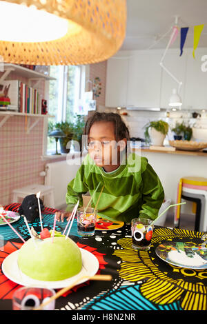 Girl (6-7) blowing candles on birthday cake - Stock Photo