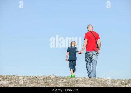 Father with son (14-15) holding hands - Stock Photo