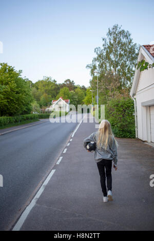 Girl (12-13) walking with soccer ball on roadside - Stock Photo
