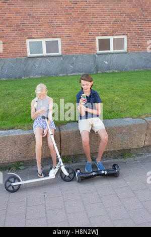 Girl (12-13) with scooter and boy (14-15) with hoverboard sitting on wall and using phones - Stock Photo