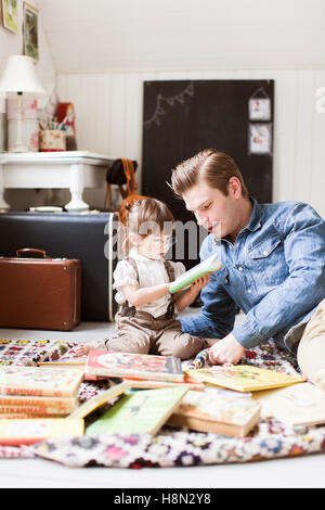 Father reading with daughter (2-3) picture book - Stock Photo