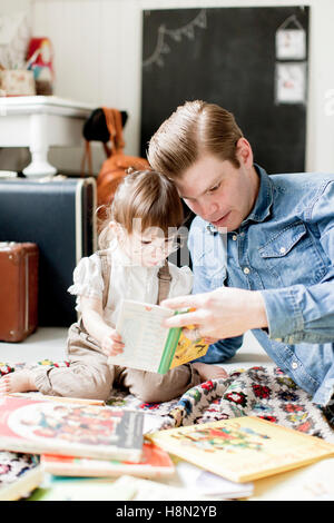 Father reading picture book with daughter (2-3) - Stock Photo