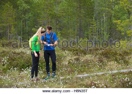 Man and woman looking at map - Stock Photo