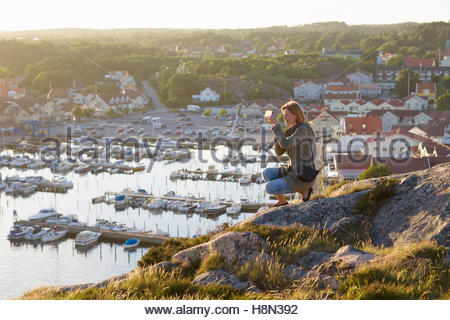 Mid adult woman taking pictures from rock overlooking port and bay - Stock Photo