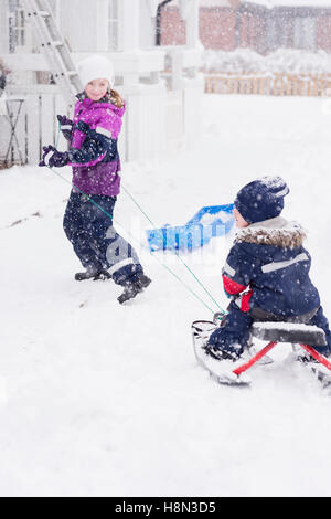 Girl (10-11) pulling brother (2-3) on sled - Stock Photo