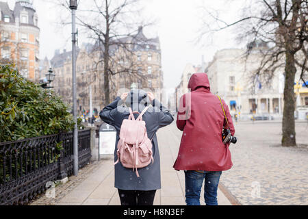Young couple walking through city in falling snow - Stock Photo