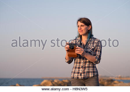Woman photographing with analog camera - Stock Photo
