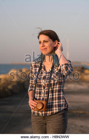 Woman in plaid shirt with analog camera - Stock Photo