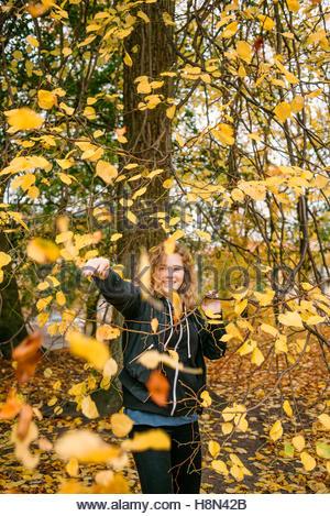 Leaves falling on girl (16-17) in park - Stock Photo