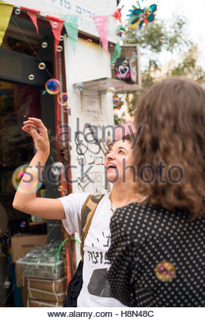 Woman looking on bubbles in street - Stock Photo