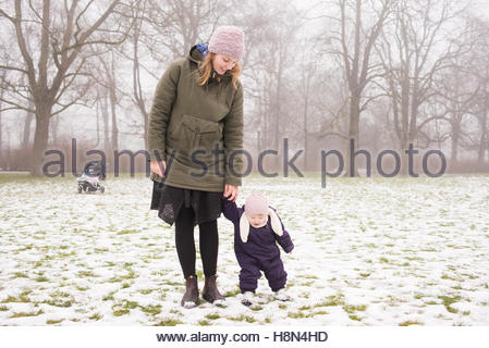 Young woman with daughter (12-17 months) in park - Stock Photo