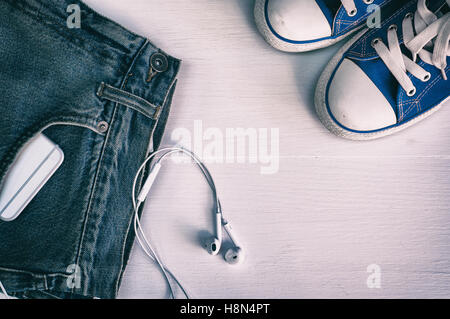 Blue worn jeans with a smartphone in the pocket, and blue sneakers on a white wooden background, vintage toning - Stock Photo