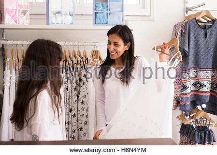 Mature woman and girl (10-11) in clothes store - Stock Photo