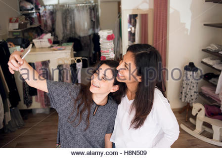 Mature woman and girl (10-11) taking selfie in clothes store - Stock Photo
